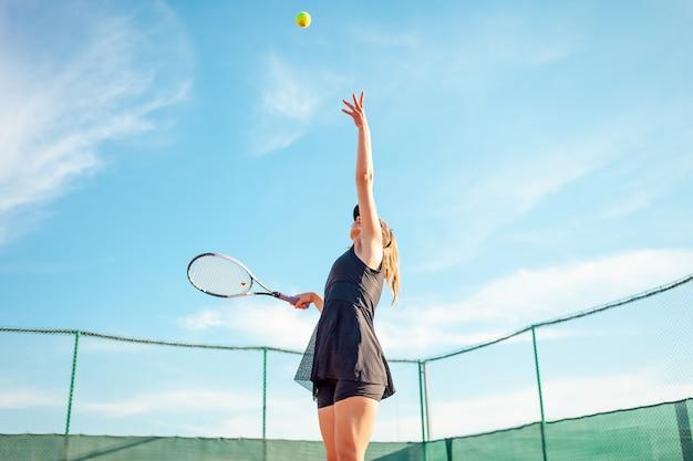 Bella giovane donna in abiti sportivi neri che giocano a tennis in campo