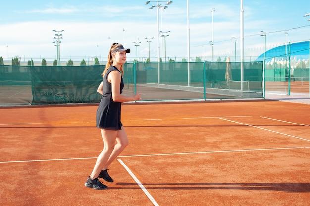 Bella giovane donna in abiti sportivi neri corre nel campo da tennis