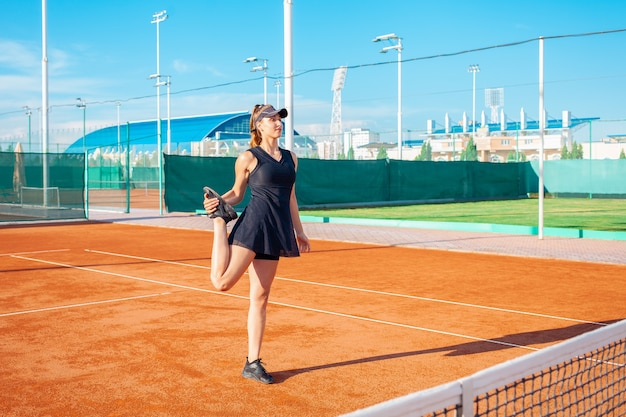 Bella giovane donna in abiti sportivi neri si estende nel campo da tennis