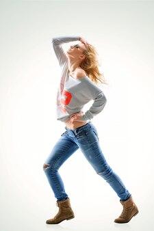 Bella giovane donna bionda in maglietta e jeans su sfondo bianco