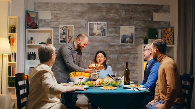 Candele di salto della bella giovane donna sulla torta di compleanno. torta deliziosa. cena di famiglia. colpo al rallentatore
