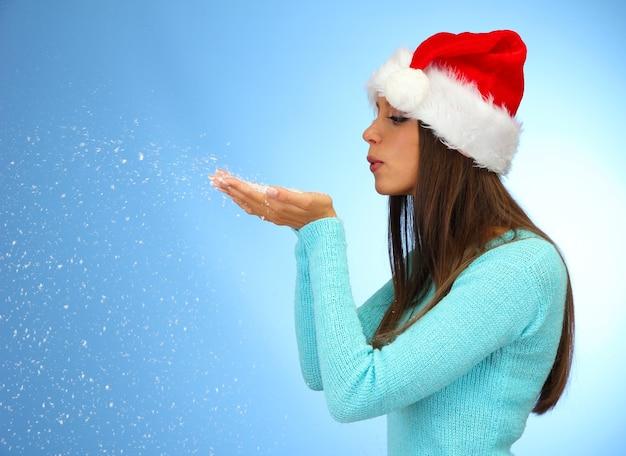 Bella giovane donna che soffia neve, su sfondo blu