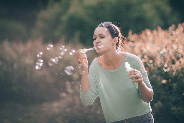 Bella giovane donna che soffia bolle di sapone nel parco soleggiato. foto con copia spazio