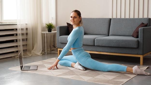 Bella giovane donna in un vestito blu che fa esercizio di forma fisica a casa. guarda il suo laptop e ripete i movimenti per il corso online.