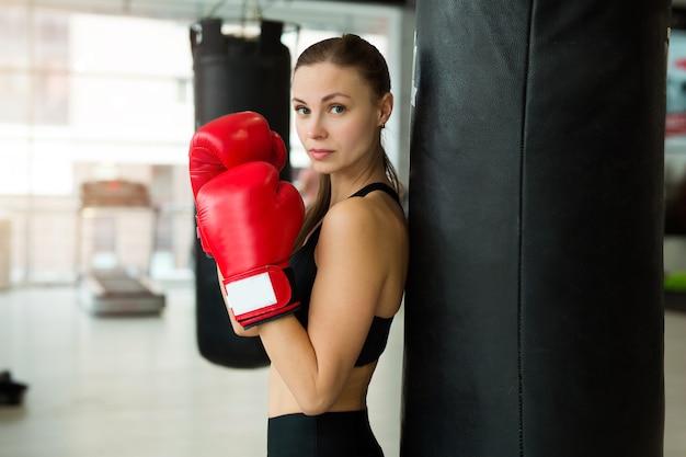 Bella giovane donna in guantoni da boxe vicino al sacco da boxe in palestra in allenamento