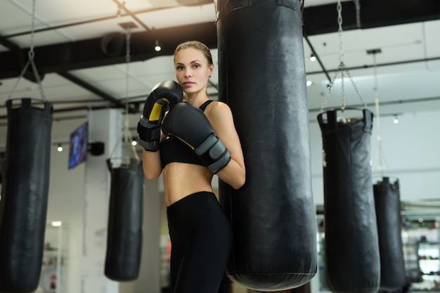 Bella giovane donna in guantoni da boxe durante la formazione