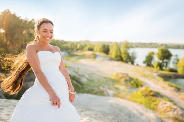 Bella sposa della giovane donna che posa sulla sabbia bianca