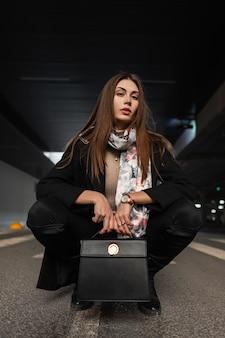 Bella giovane donna bruna in abiti eleganti di eleganza nera con borsa in pelle alla moda è seduta sull'asfalto in città. ragazza europea moderna alla moda in posa sulla strada in strada.