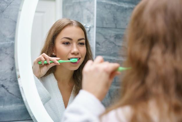 Una bellissima giovane donna si lava i denti e si guarda allo specchio