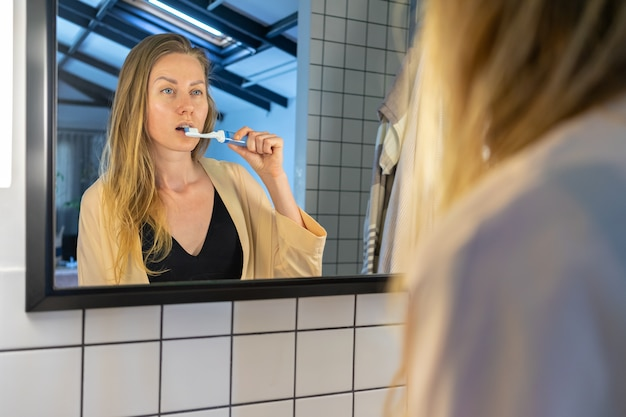 Bella giovane donna che pulisce i suoi denti davanti allo specchio del bagno