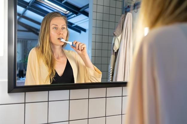 Bella giovane donna che pulisce i suoi denti con lo spazzolino da denti davanti allo specchio del bagno.