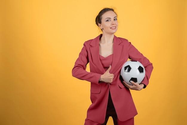 Bella giovane donna d'affari con pallone da calcio in posa su sfondo giallo. mostra pollice in su