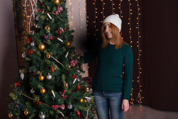 Bella giovane donna con un berretto e un maglione sorridente e in piedi vicino all'albero di natale