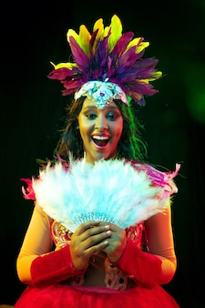 Bella giovane donna in maschera di carnevale e costume in maschera a luci colorate