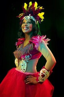 Bella giovane donna in maschera di carnevale ed elegante costume in maschera con piume in luci colorate e bagliore sul muro nero