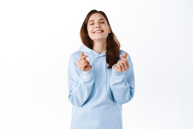 Bella giovane donna in felpa con cappuccio blu casual, che mostra i cuori delle dita e sorride carina davanti, concetto di emozioni positive, in piedi sul muro bianco