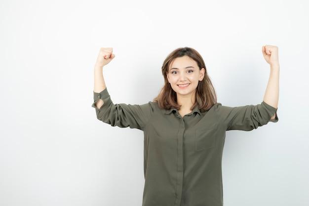 Bella giovane donna in abbigliamento casual che mostra i suoi muscoli.