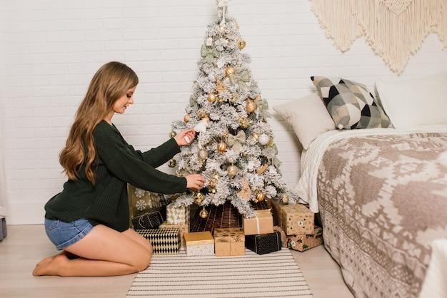 Bella giovane donna che celebra il natale a casa, divertendosi mentre apre i regali