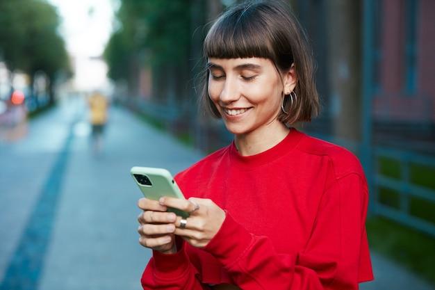 Bella giovane donna in chat sul telefono in strada, donna millenaria carina in maglione rosso alla moda con smartphone e sorridente