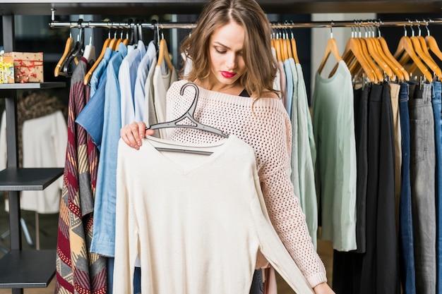 Bella giovane donna che sceglie i vestiti mentre compera al negozio di vestiti