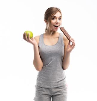 Bella giovane donna che sceglie tra cibo sano e malsano frutta o dolci