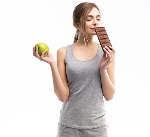 Bella giovane donna che sceglie tra cibo sano e malsano