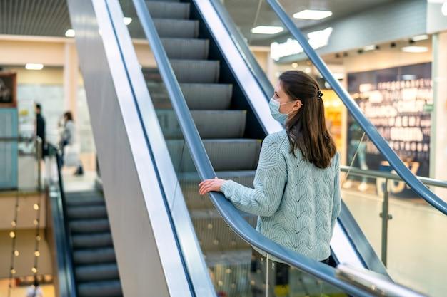 Una bellissima giovane donna sale la scala mobile di un centro commerciale con una maschera protettiva