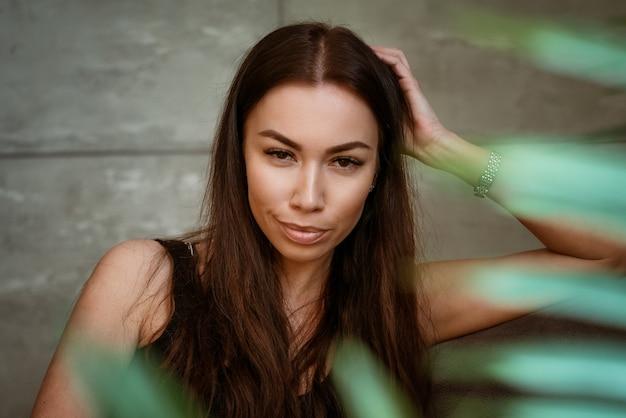 Ritratto del primo piano della bella giovane donna attraverso le foglie verdi di un fiore su un muro grigio
