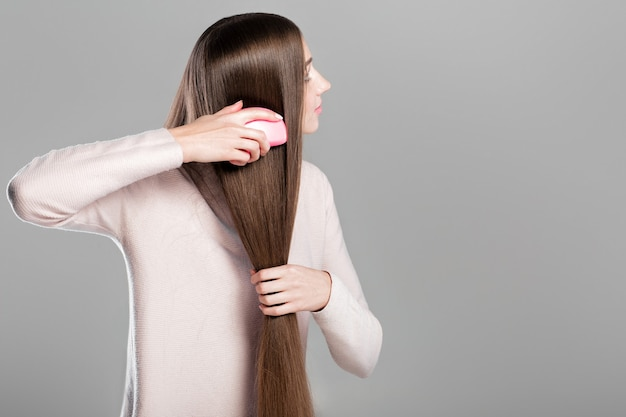 Bella giovane donna che pettina i suoi capelli naturali lunghi lisci con la spazzola per capelli