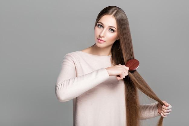 Bella giovane donna che pettina i suoi lunghi capelli naturali lisci con una spazzola per capelli in legno