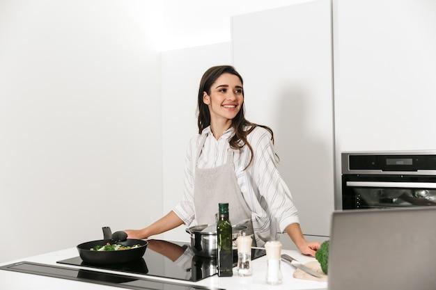 Bella giovane donna che cucina una cena sana in cucina