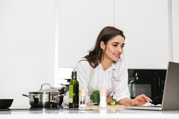 Bella giovane donna che cucina una cena sana in una pentola in cucina, guardando il computer portatile