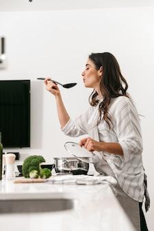 Bella giovane donna che cucina una cena sana in una pentola in cucina