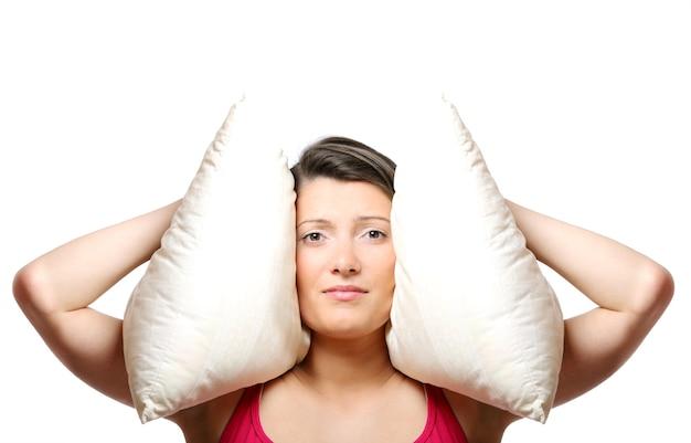 Una bellissima giovane donna che si copre le orecchie con un cuscino su sfondo bianco