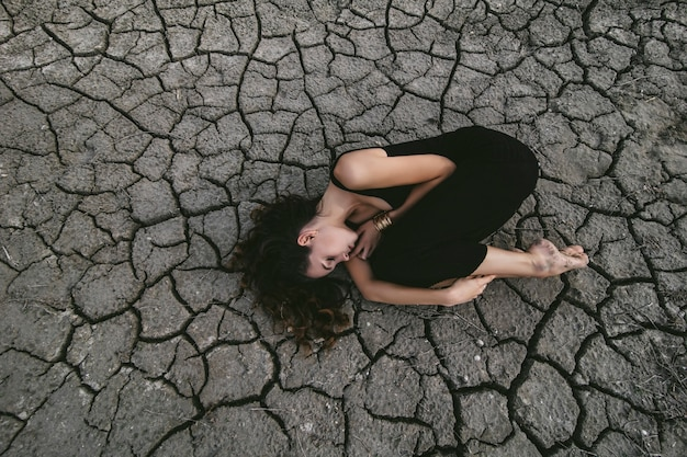 Bella giovane donna sulla terra screpolata in abito nero