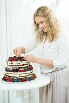 Bella giovane donna decora una torta a tre livelli con frutti di bosco