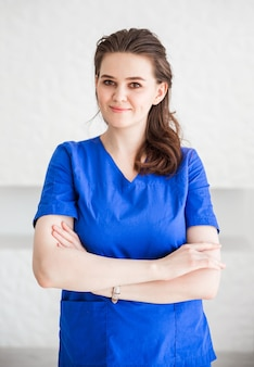 Bello medico della giovane donna che posa in vestito medico blu.