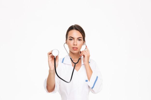 Bella giovane donna medico indossa uniforme in piedi isolato su muro bianco, utilizzando uno stetoscopio