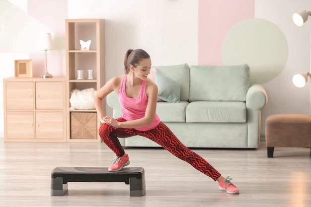 Bella giovane donna facendo esercizio di fitness a casa