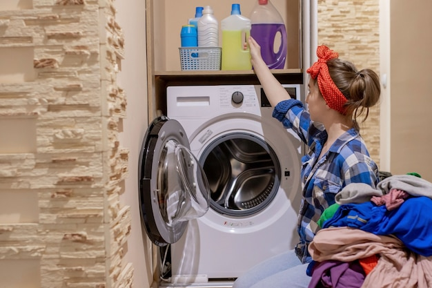 Bella giovane donna che fa lavanderia. lavori di casa.