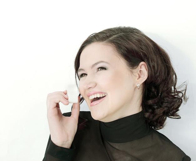Bella giovane donna che fa trucco. isolato su un muro bianco
