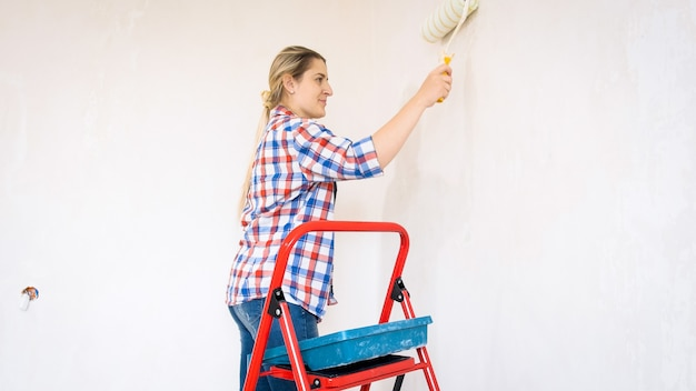 Bella giovane donna che fa lavori di ristrutturazione a casa e dipinge pareti con rullo.
