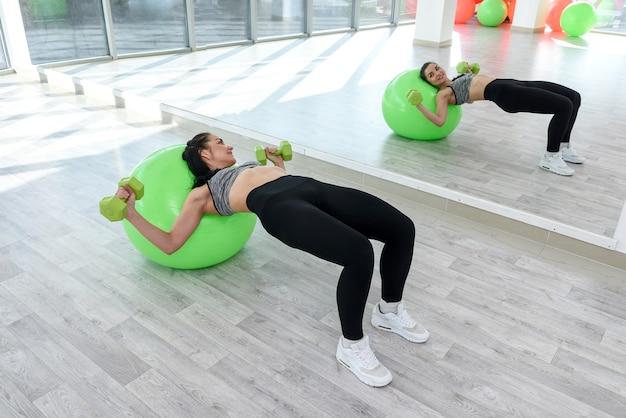 Bella giovane donna che fa esercizio di forza sulla palla adatta in studio di classe di aerobica. fitness femminile come stile di vita e salute.
