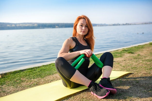 Bella giovane donna che fa esercizio di stretching prima dell'orario di lavoro la mattina al parco