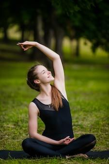 Bella giovane donna che fa esercizio di stretching sull'erba verde al parco