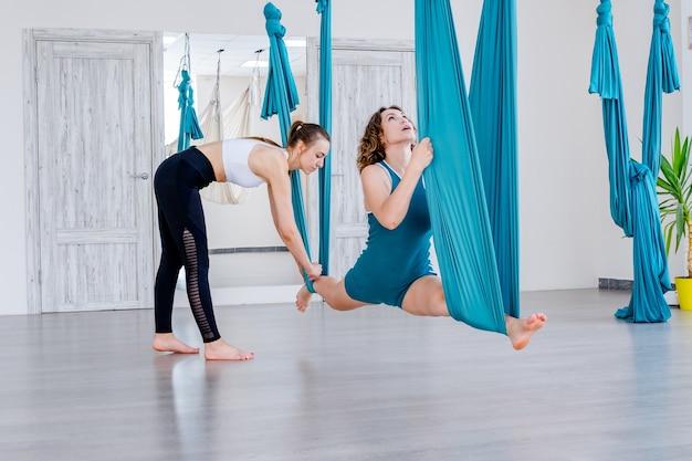 Bella giovane donna che fa stretching yoga posa utilizzando amaca con trainer in studio