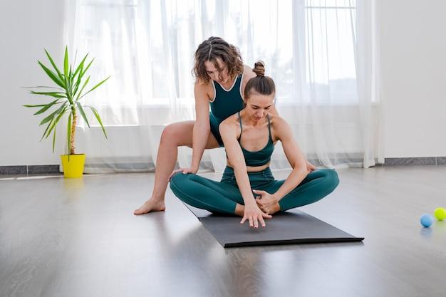 Bella giovane donna che fa yoga con l'istruttore in studio