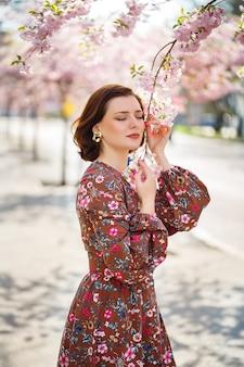 Bella giovane donna in un vestito in alberi di sakura in fiore. fuori è una calda giornata di sole primaverile