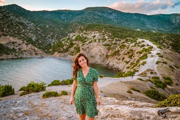 Una bella giovane donna in un vestito a capo kapchik nella romantica vista sul mare della crimea
