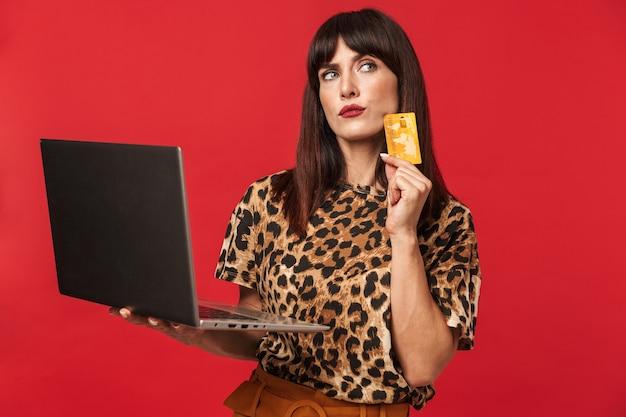 Bella giovane donna vestita in camicia stampata animale in posa isolata sul muro rosso utilizzando il computer portatile in possesso di carta di credito.